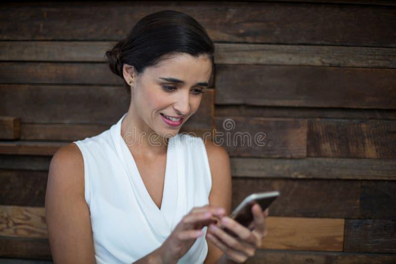 Uśmiechnięty żeński dyrektor wykonawczy używa telefon komórkowego fotografia royalty free