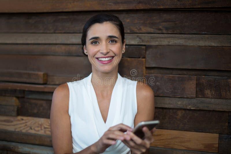 Uśmiechnięty żeński dyrektor wykonawczy używa telefon komórkowego obrazy royalty free