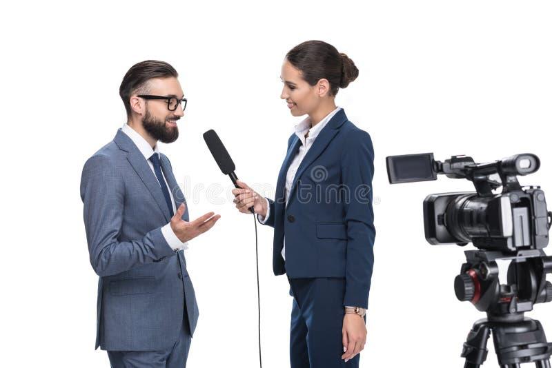 uśmiechnięty żeński dziennikarz przeprowadza wywiad biznesmena z mikrofonem i kamera wideo, fotografia stock
