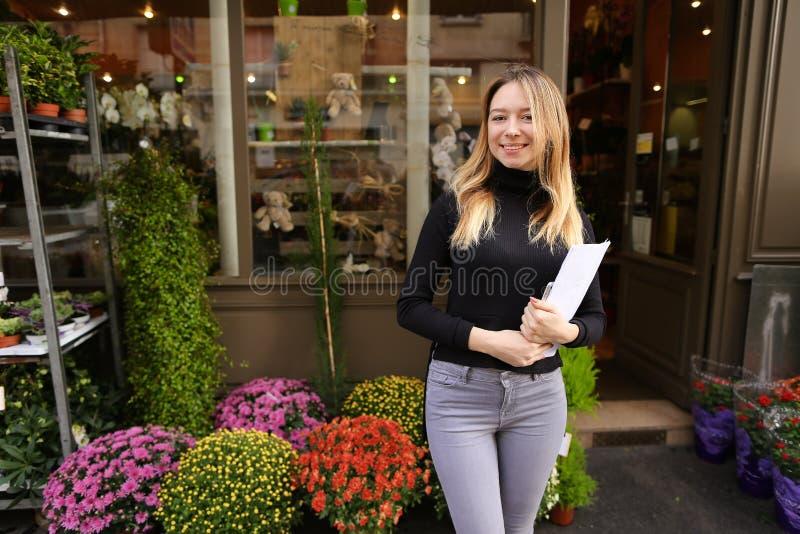 Uśmiechnięty żeński kierownik kwiatu sklepu pozycja z papierami zdjęcia stock
