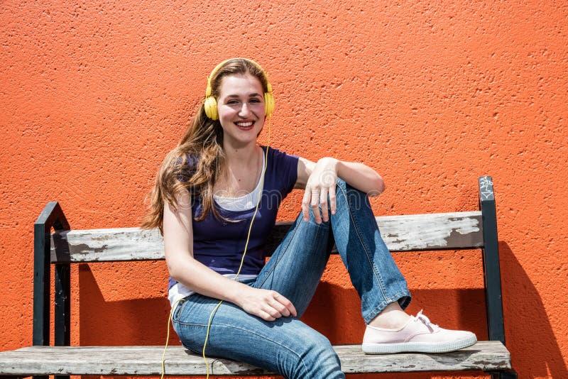 Uśmiechnięty żeński nastolatek słucha muzyka w jej kolorowych hełmofonach obraz stock