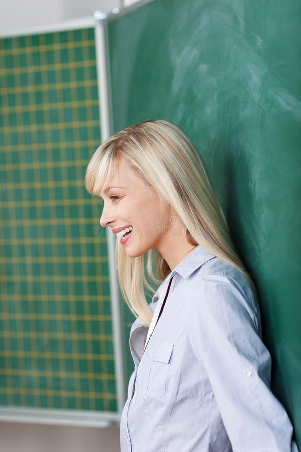 Uśmiechnięty żeński opierać przy deską zdjęcie stock