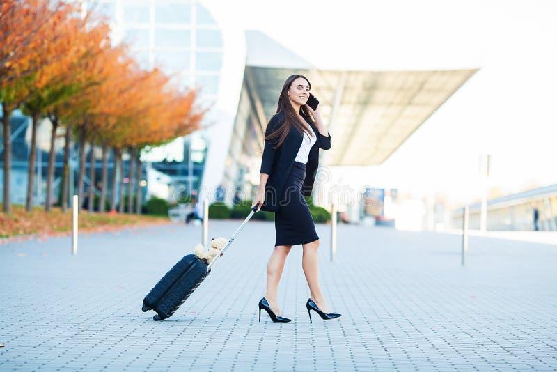 Uśmiechnięty żeński pasażerski postępowanie wyjście bramy ciągnięcia walizka przez lotniskowego concourse obraz stock