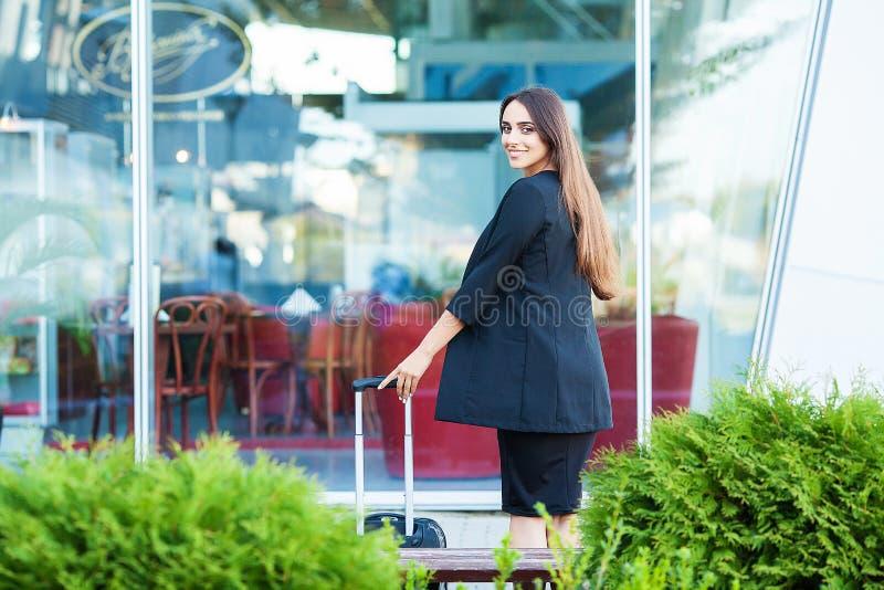 Uśmiechnięty żeński pasażerski postępowanie wyjście bramy ciągnięcia walizka przez lotniskowego concourse fotografia royalty free