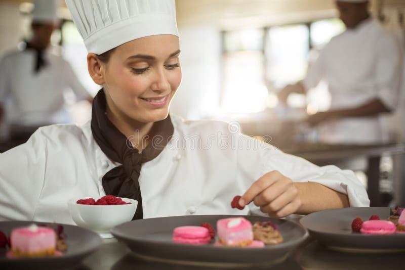 Uśmiechnięty żeński szef kuchni kończy deserowych talerze obrazy stock