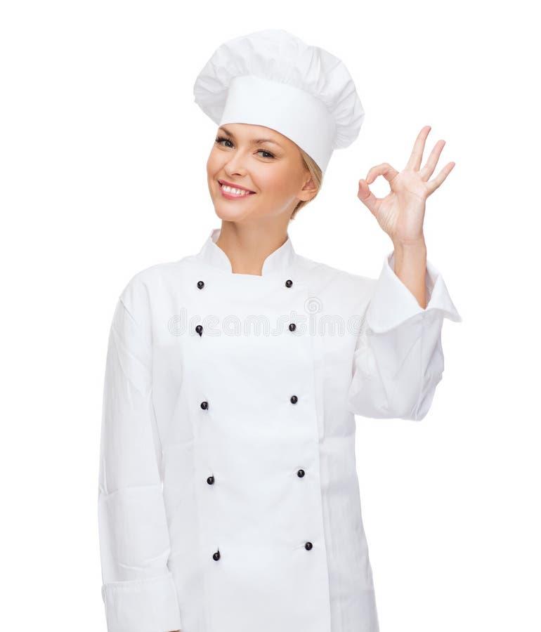 Uśmiechnięty żeński szef kuchni pokazuje ok ręka znaka zdjęcia royalty free