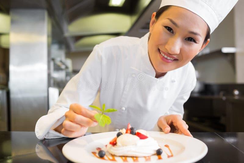 Uśmiechnięty żeński szefa kuchni garnirowania jedzenie w kuchni obraz royalty free