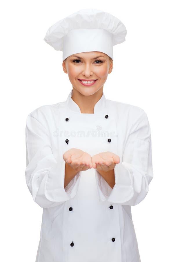 Uśmiechnięty żeński szefa kuchni mienie coś na rękach fotografia stock