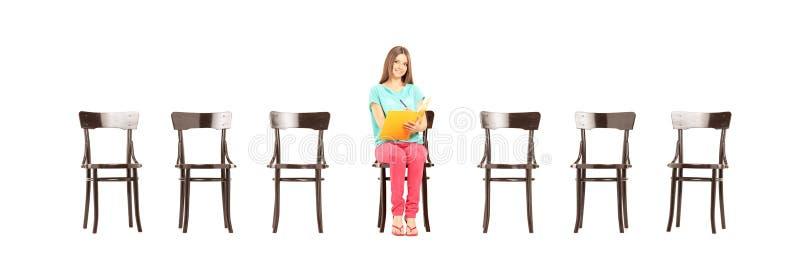 Uśmiechnięty żeńskiego ucznia obsiadanie na drewnianym writing i krześle nie zdjęcia stock