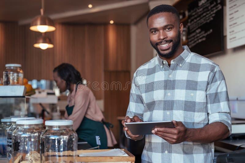 Uśmiechnięty Afrykański przedsiębiorca pracuje przy kontuarem jego kawiarnia obrazy royalty free