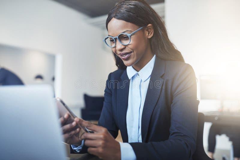 Uśmiechnięty amerykanin afrykańskiego pochodzenia bizneswoman używa jej telefon komórkowego w zdjęcia royalty free