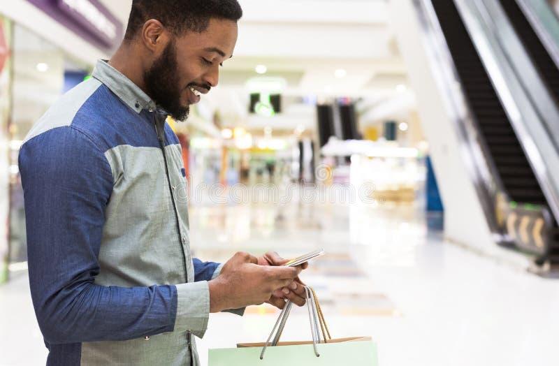 Uśmiechnięty amerykanin afrykańskiego pochodzenia faceta gmeranie przez interneta zdjęcia royalty free