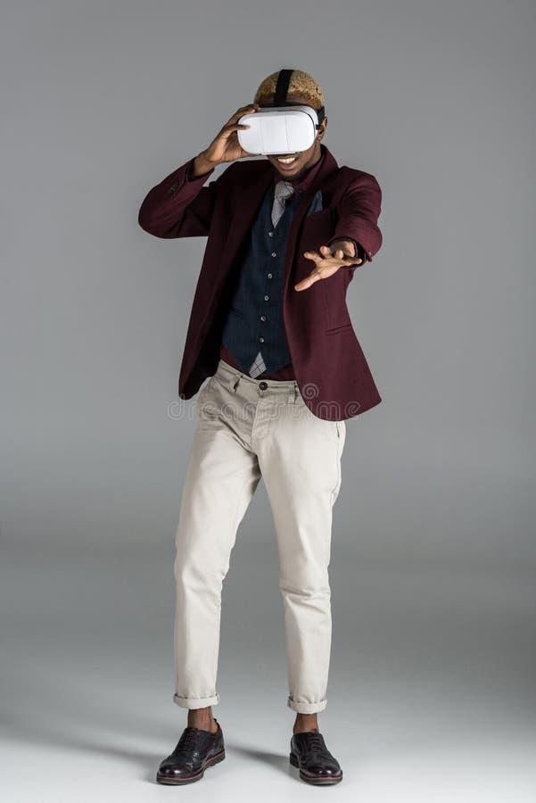 uśmiechnięty amerykanina afrykańskiego pochodzenia mężczyzna w vr szkłach z ręką szeroko rozpościerać na popielatym tle obraz royalty free