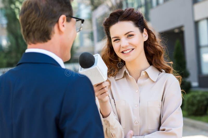 uśmiechnięty anchorwoman z mikrofonu przeprowadzać wywiad obraz royalty free