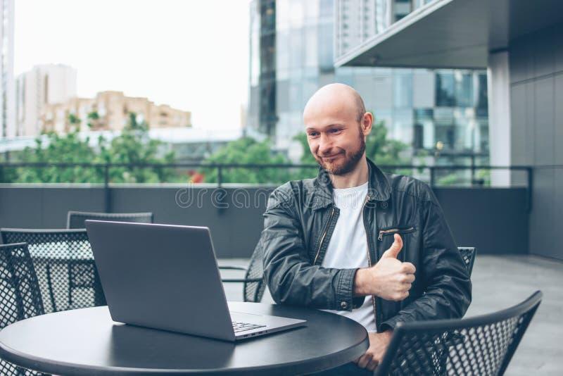 Uśmiechnięty atrakcyjny dorosły pomyślny łysy brodaty mężczyzna w czarnej kurtce z laptopem w ulicznej kawiarni przy miastem obrazy royalty free