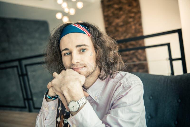 Uśmiechnięty atrakcyjny młody artysta z jaskrawymi niebieskimi oczami obrazy stock