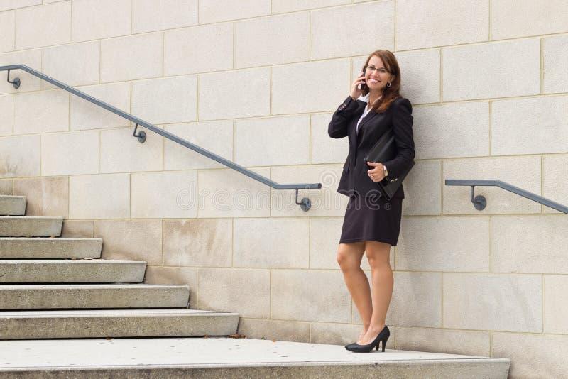 Uśmiechnięty atrakcyjny młody biznesowej kobiety kierownictwo opowiada na telefonie zdjęcia royalty free