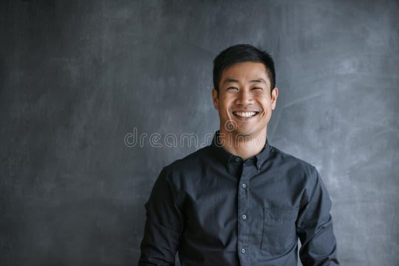 Uśmiechnięty Azjatycki biznesmen stoi bezczynnie pustego biurowego chalkboard obrazy royalty free