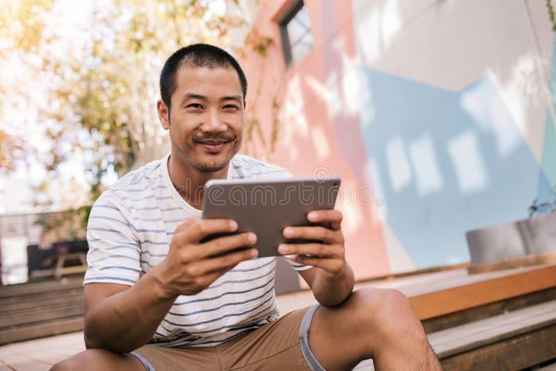 Uśmiechnięty Azjatycki mężczyzna obsiadanie na schodkach na zewnątrz używać pastylkę zdjęcia royalty free