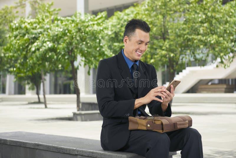 Uśmiechnięty azjatykci biznesmen używa telefon komórkowego obrazy stock
