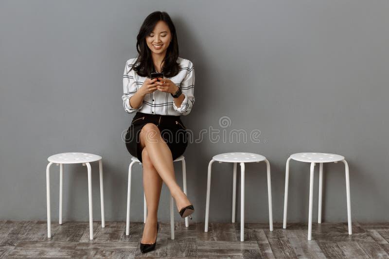 uśmiechnięty azjatykci bizneswoman z smartphone czekaniem fotografia stock