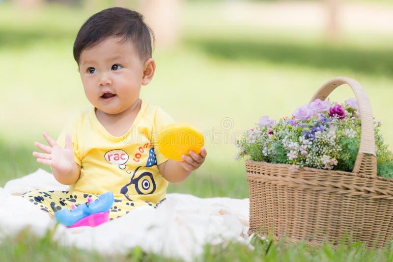 Uśmiechnięty azjatykci chłopiec berbeć siedzi na białej bawełnie w zielonych gras obrazy royalty free
