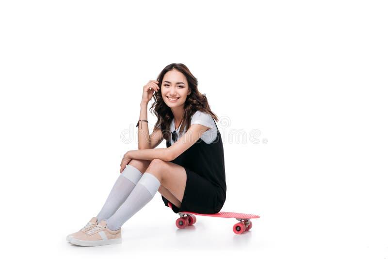 Uśmiechnięty azjatykci dziewczyny obsiadanie na deskorolka i patrzeć kamerę zdjęcie royalty free
