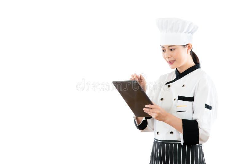 Uśmiechnięty azjatykci kobieta szef kuchni używa cyfrową pastylkę fotografia royalty free