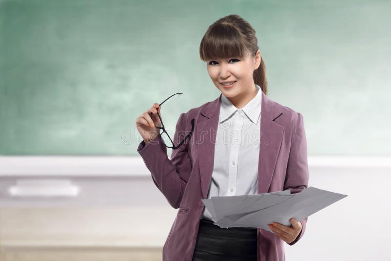Uśmiechnięty azjatykci nauczyciel z papierową pozycją przed blackboard fotografia stock