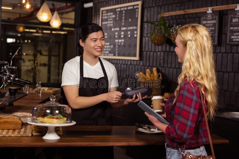 Uśmiechnięty barista bierze kredytową kartę od klienta obraz royalty free