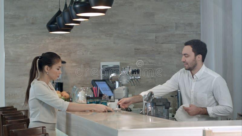 Uśmiechnięty barista opowiada żeński klient kończy jej napój obraz royalty free