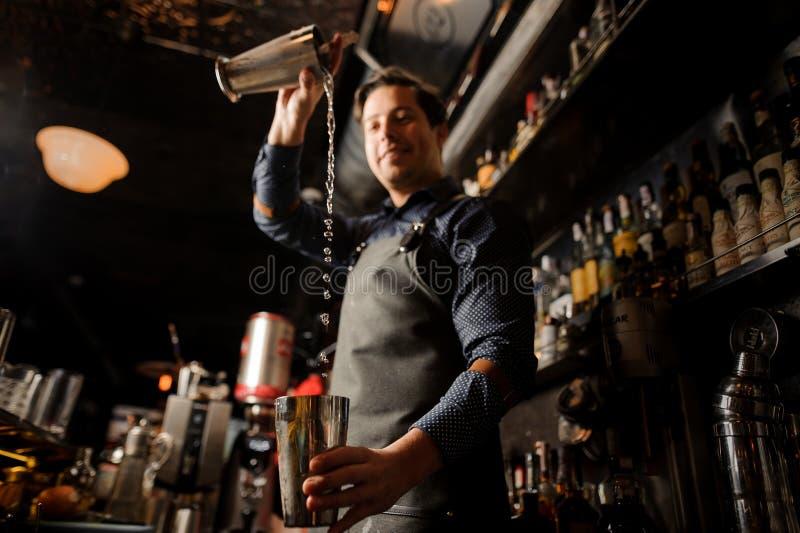 Uśmiechnięty barman nalewa alkoholicznego napój od jeden metalu szkła w inny fotografia stock