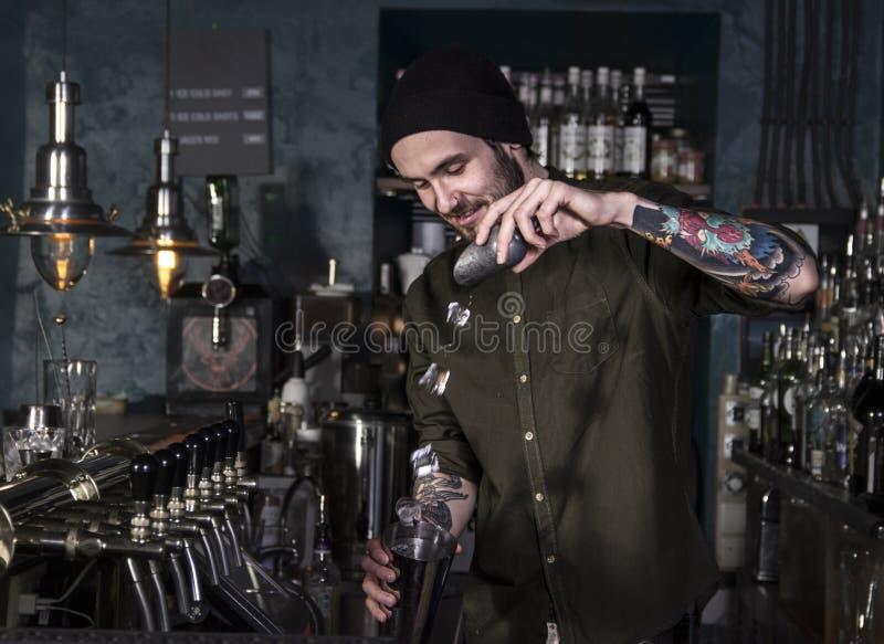 Uśmiechnięty barman robi koktajlowi obraz stock