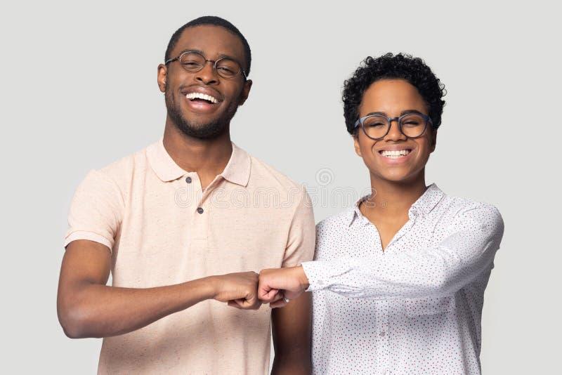 Uśmiechnięty biracial mężczyzna i kobieta dajemy pięść garbka śmiać się fotografia stock
