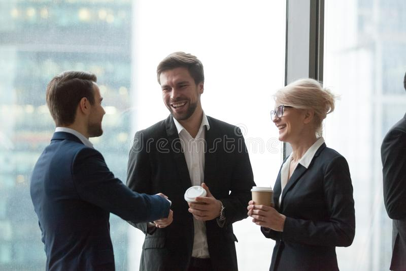 Uśmiechnięty biurowych pracowników powitanie podczas kawowej przerwy zdjęcie royalty free