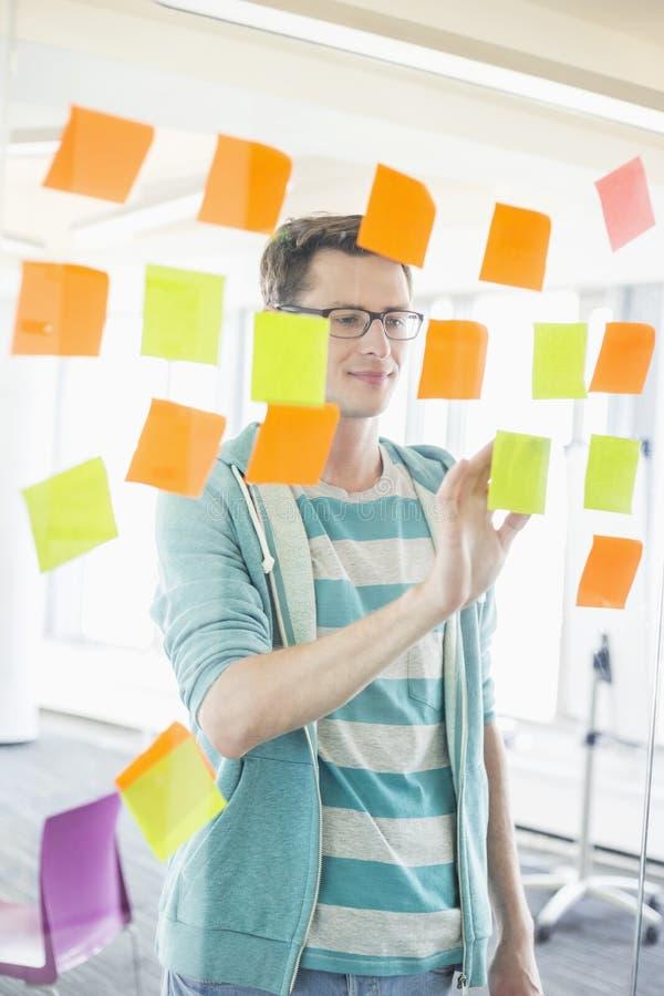 Uśmiechnięty biznesmen czyta kleiste notatki na szklanej ścianie w kreatywnie biurze fotografia stock