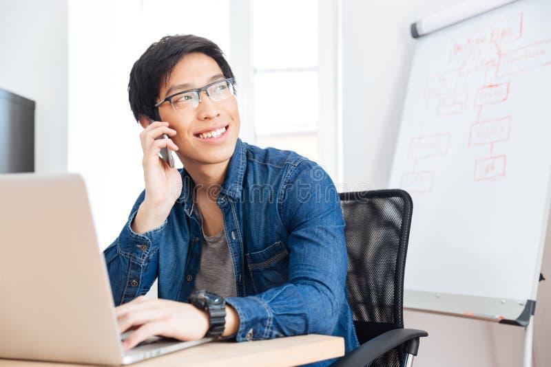 Uśmiechnięty biznesmen opowiada na telefonie komórkowym w biurze z laptopem obraz royalty free