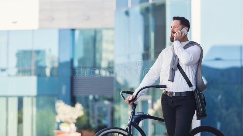 Uśmiechnięty biznesmen opowiada nad telefon komórkowy pozycją z bicyklem zdjęcia royalty free