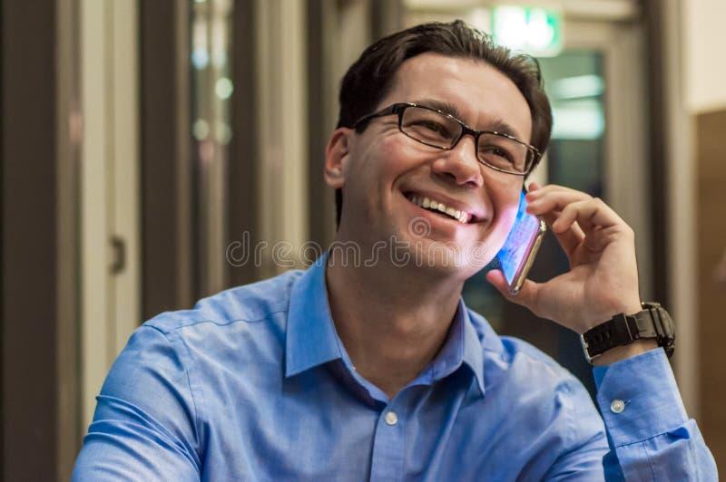 Uśmiechnięty biznesmen opowiada przy kawiarnią biznesmena szczęśliwy telefon komórkowy używać obraz royalty free