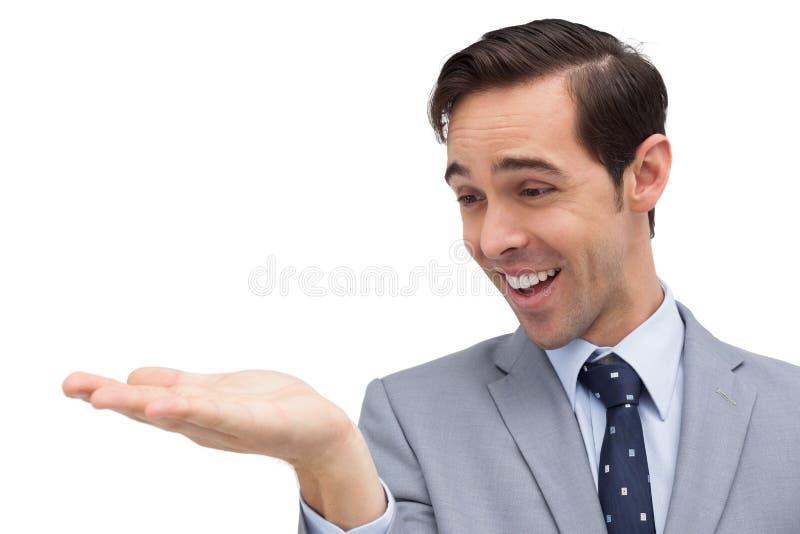 Uśmiechnięty biznesmen patrzeje i pokazuje jego rozpieczętowaną rękę zdjęcia stock