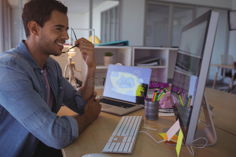 Uśmiechnięty biznesmen patrzeje komputer w biurze fotografia stock