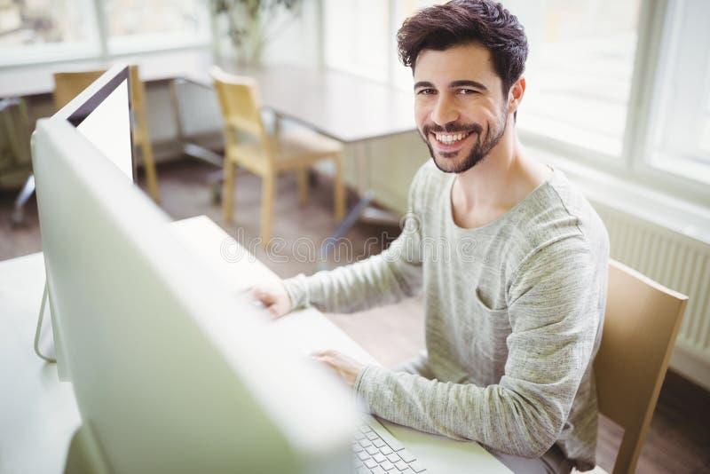 Uśmiechnięty biznesmen pracuje przy biurkiem w biurze obrazy stock