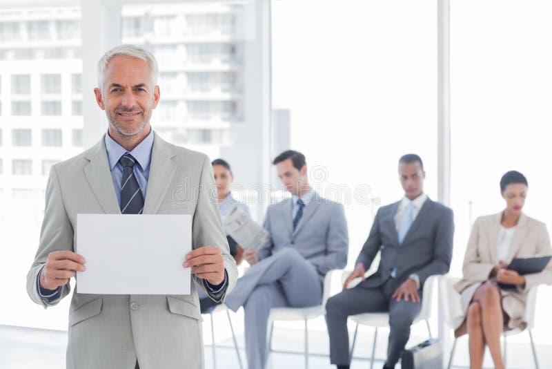 Uśmiechnięty biznesmen trzyma pustego zawiadomienie zdjęcia royalty free