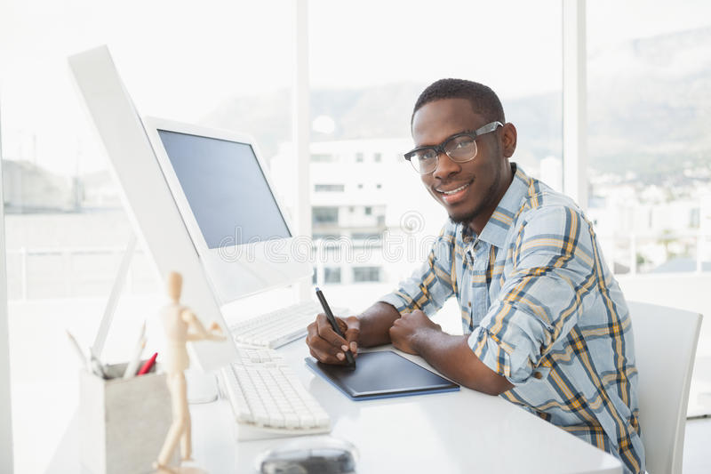 Uśmiechnięty biznesmen używa digitizer przy biurkiem zdjęcia stock