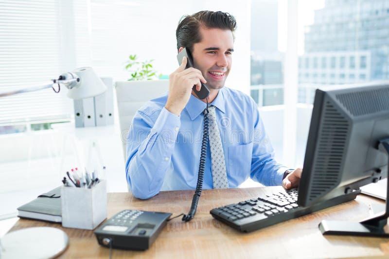 Uśmiechnięty biznesmen używa jego komputeru ans telefonowanie obrazy royalty free