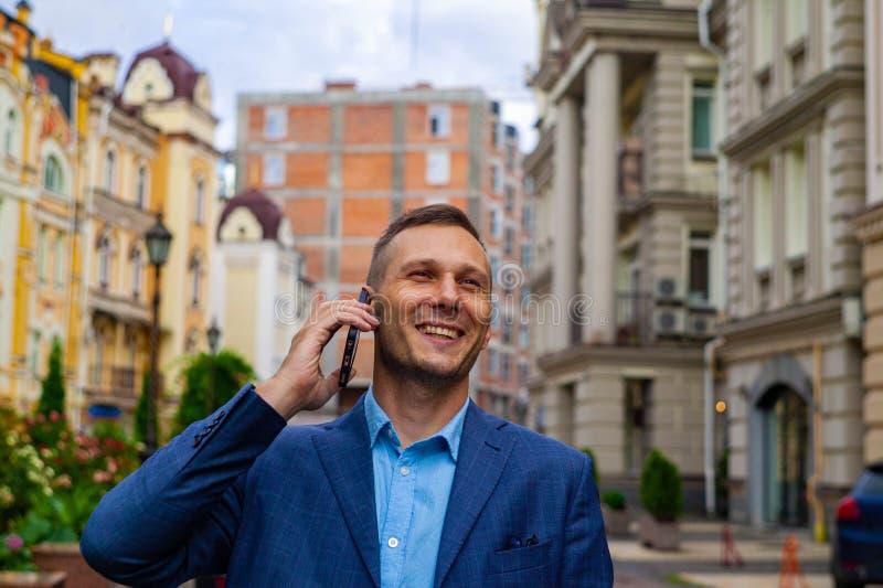 Uśmiechnięty biznesmen używa telefon w mieście fotografia stock