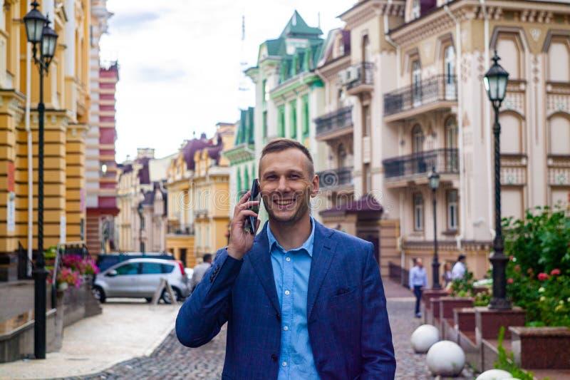 Uśmiechnięty biznesmen używa telefon w mieście zdjęcie royalty free