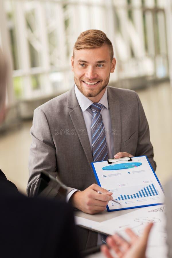 Uśmiechnięty biznesmen z wykresem przy biznesowym spotkaniem obrazy stock