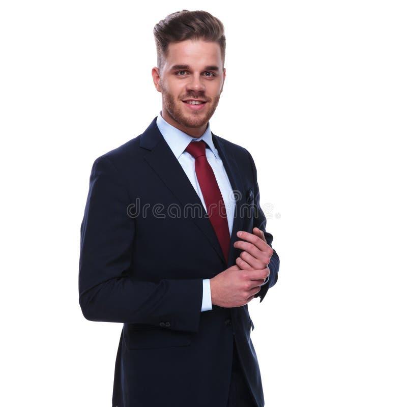Uśmiechnięty biznesmen załatwia jego rękawy w marynarka wojenna kostiumu i czerwonym krawacie obraz royalty free