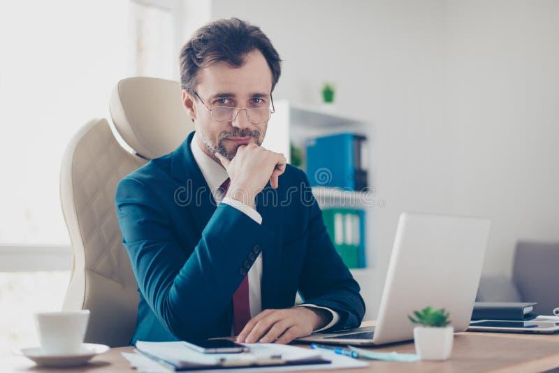 Uśmiechnięty biznesmena bankowiec siedzi przy jego looki i miejscem pracy zdjęcie stock
